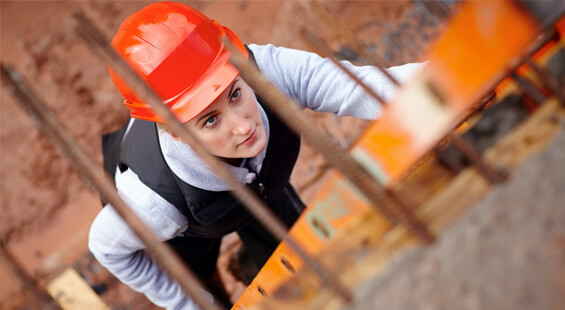 young construction worker in an orange hardhat climbing up a ladder