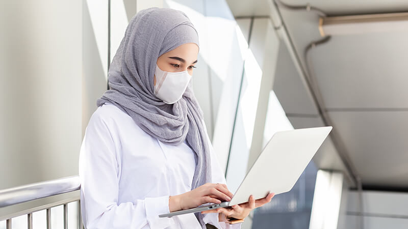 woman wearing a grey hijab and mask using a laptop
