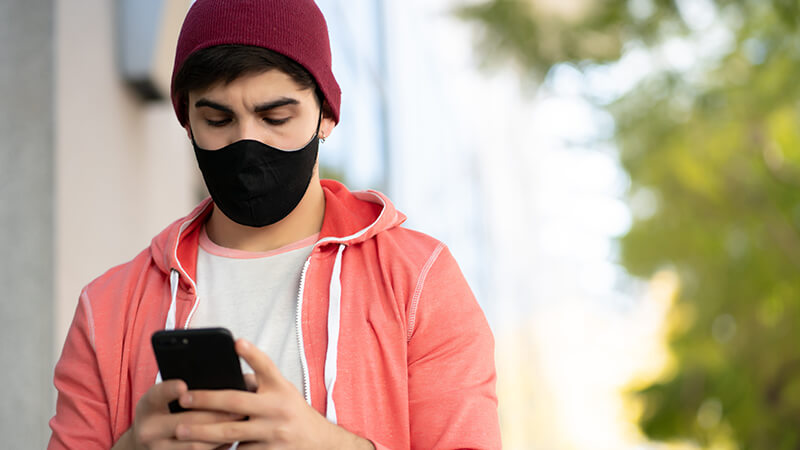 man wearing a tight fitting beanie in a hoodie and wearing a mask looking down at a mobile phone