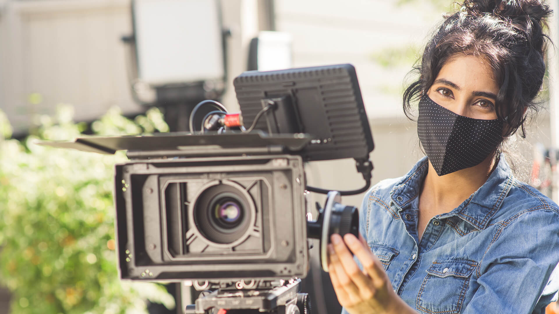 woman in mask standing behind a camera