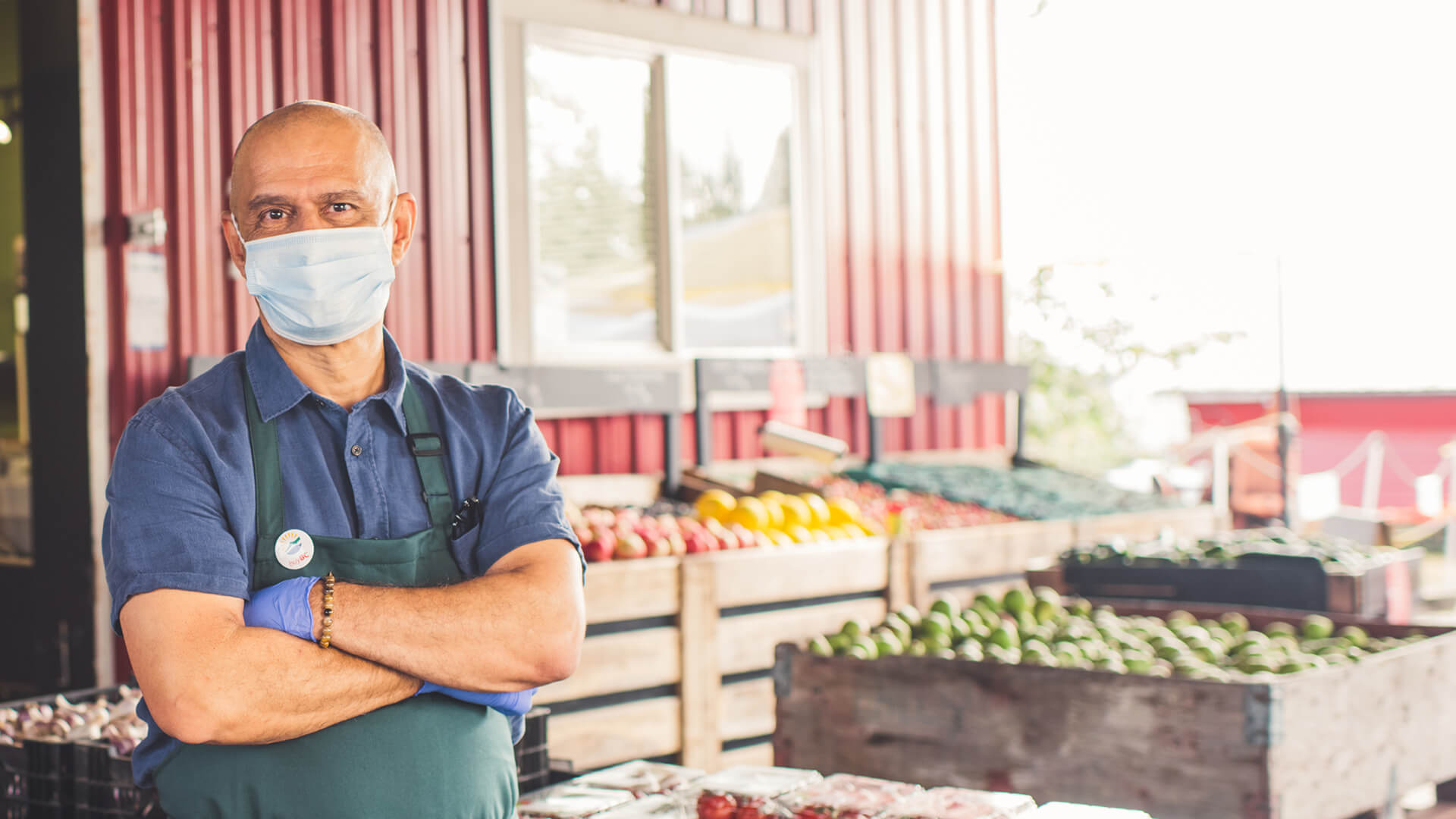 man in mask standing in front of a produce store