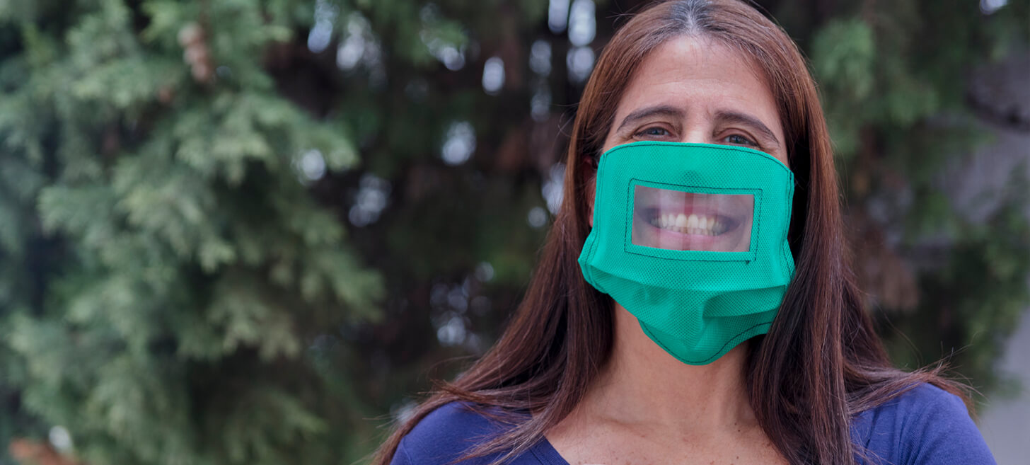 woman wearing a green bordered face mask with a see through shield insert grinning