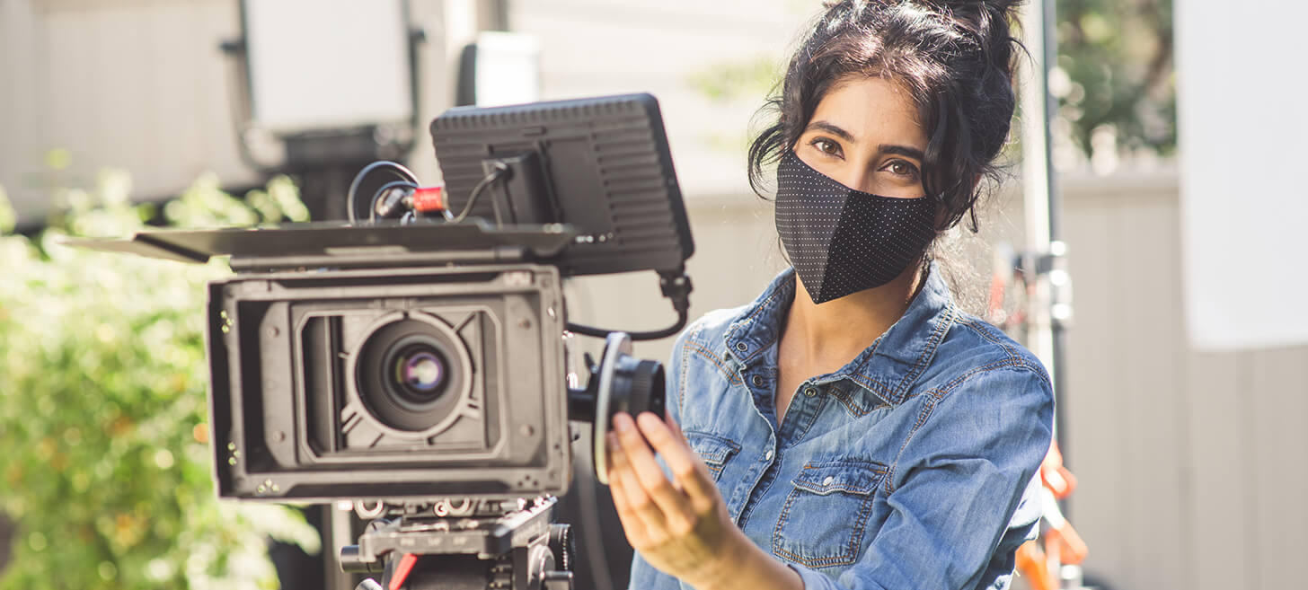 woman in mask standing behind a video camera