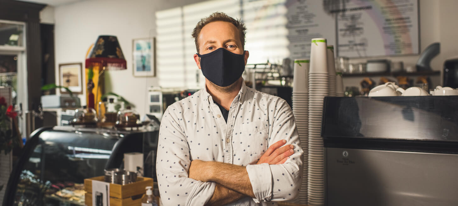 barista in coffee shop wearing a mask