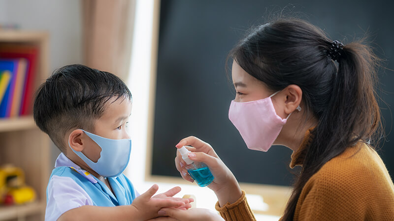 early childhood educator with small child both wearing masks