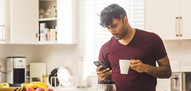 man in a t-shirt holding a coffee cup in one hand and a mobile phone in the other