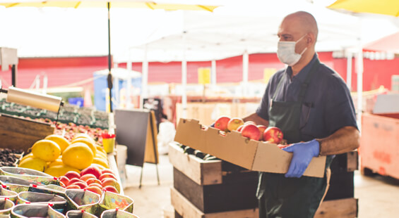 man wearing a mask carrying box of apples in a produce store