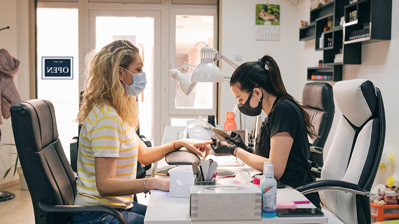 two women wearing masks sitting across from each other while one works on the others nails in an aesthetician salon